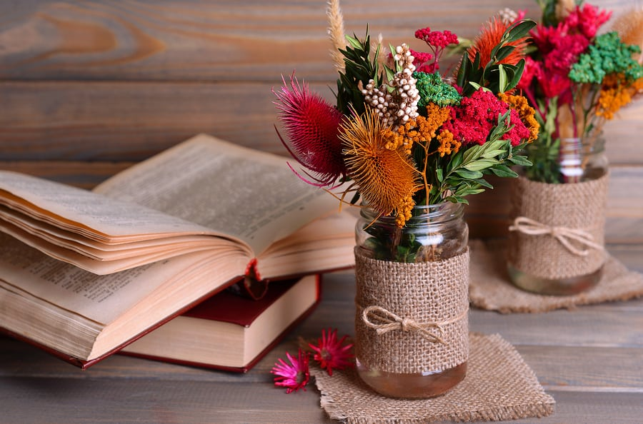 Beautiful bouquet of bright flowers in jars on table on grey bac