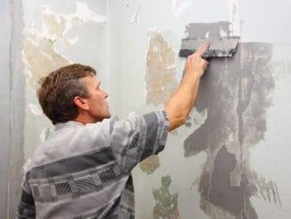 barbat care repara tencuiala unui perete