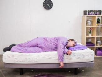 barbat imbracat in mov care doarme pe un pat cu saltea relaxa