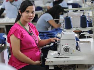 femeie insarcinata lucrand in croitorie
