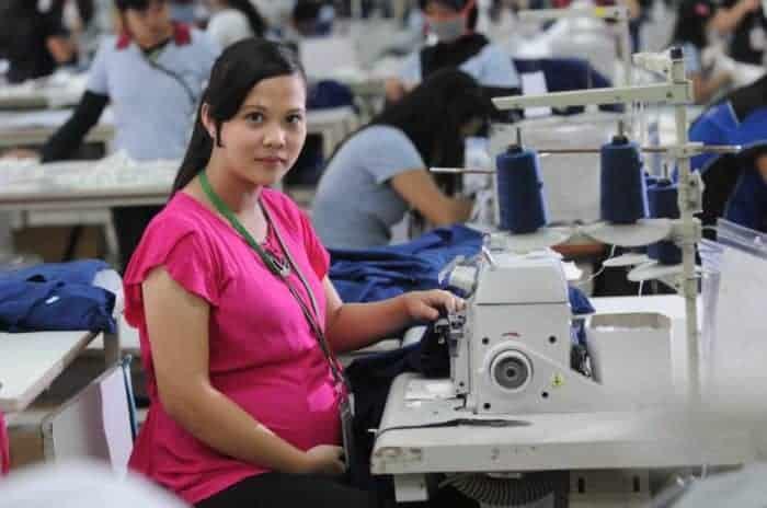 femeie insarcinata muncind in fabrica de textile